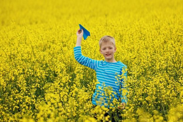 Młoda chłopiec z papierowym samolotem przeciw niebieskiemu niebu