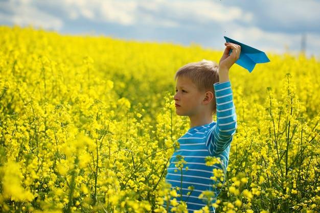 Młoda chłopiec z papieru samolotem przeciw niebieskiemu niebu i żółtemu polu flo