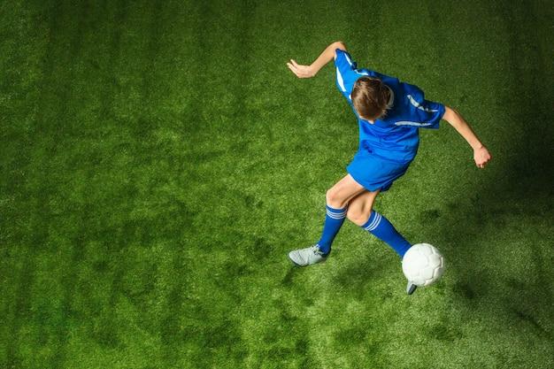 Młoda chłopiec z piłki nożnej piłką robi latającemu kopnięciu