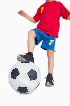 Młoda chłopiec z stopą na piłki nożnej