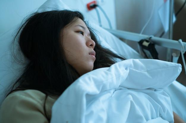 Młoda chora azjatycka cierpliwa kobieta kłama na łóżku w oddziale szpitalnym