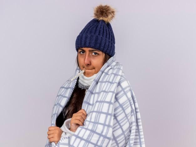 Młoda chora dziewczyna patrząc na kamery na sobie czapkę zimową z szalikiem zawiniętym w kratę umieszczając termometr w ustach na białym tle