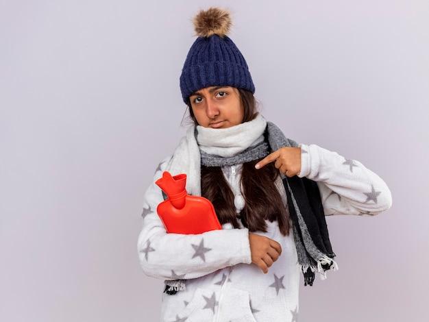 Młoda chora dziewczyna patrząc na kamery w czapce zimowej z szalikiem trzyma i wskazuje na worek ciepłej wody na białym tle