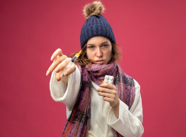 Młoda chora dziewczyna patrzy prosto przed siebie na sobie białą szatę i czapkę zimową z szalikiem trzymając pigułki i trzymając strzykawkę na różowym tle