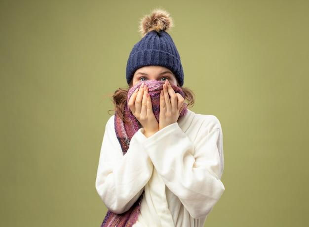 Młoda chora dziewczyna ubrana w białą szatę i czapkę zimową z szalikiem zakryta twarz szalikiem