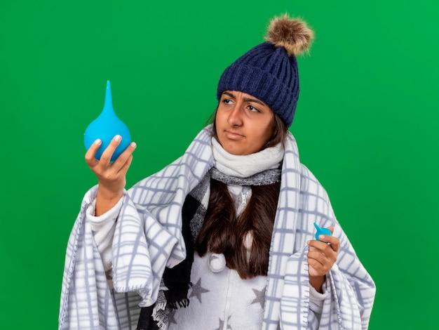 Młoda chora dziewczyna ubrana w czapkę zimową z szalikiem, trzymając i patrząc na lewatywy na białym tle na zielono