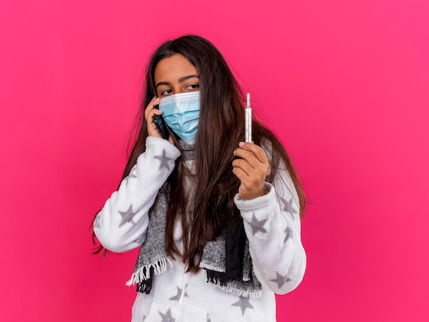 Młoda chora dziewczyna ubrana w maskę medyczną z szalikiem rozmawia przez telefon i patrząc na termometr w dłoni na różowym tle