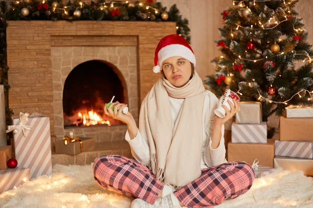 Młoda chora dziewczyna w czapce mikołaja i spodniach w kratkę, trzymając w rękach spray i kubek rozgrzewającego napoju, patrzy na aparat ze smutnym wyrazem twarzy
