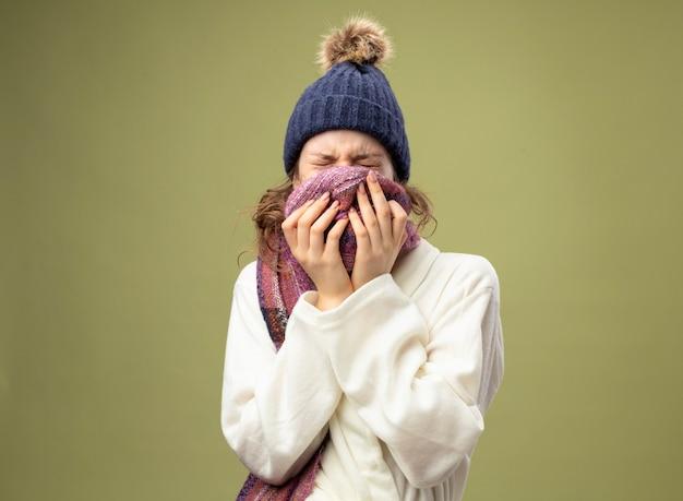 Młoda chora dziewczyna z zamkniętymi oczami w białej szacie i zimowej czapce z szalikiem zakryta twarz szalikiem