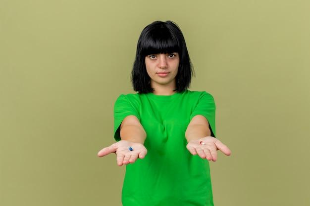 Młoda chora dziewczynka kaukaski wyciągając kapsułki medyczne w kierunku izolowanych na oliwkowej ścianie zielonej z miejsca na kopię