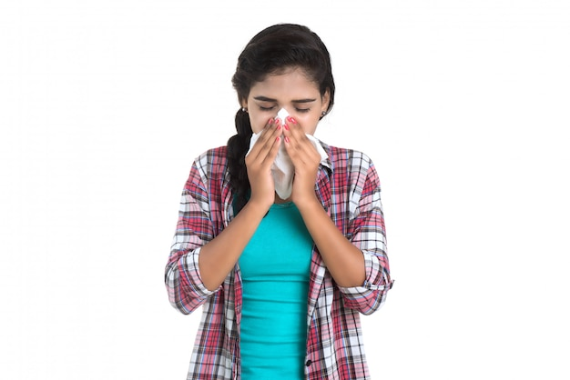Młoda chora kobieta dmucha jej nos. alergiczny nieżyt nosa. ma gorączkę młoda kobieta z zimnem
