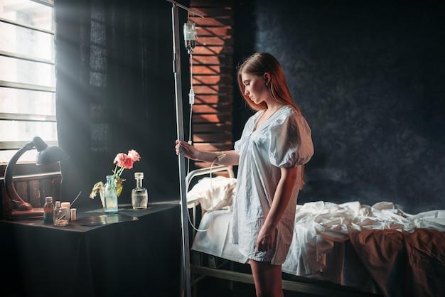Młoda chora kobieta jest na kroplówce w szpitalu