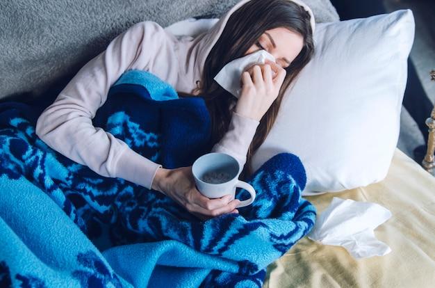Młoda chora kobieta kicha nos w chusteczkę, ma problemy zdrowotne z zatokami lub alergią. leżąc pod niebieskim kocem w łóżku