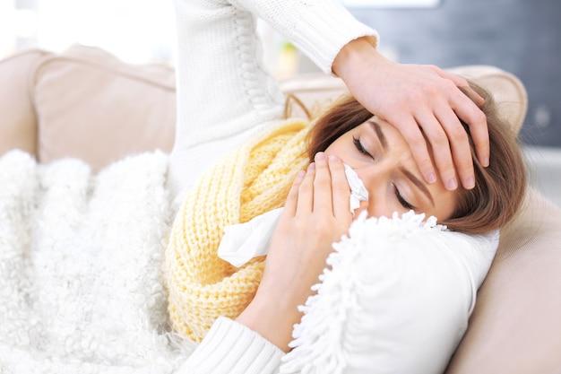 Młoda chora kobieta leżąca w łóżku w domu