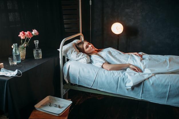 Młoda chora kobieta leży w szpitalnym łóżku