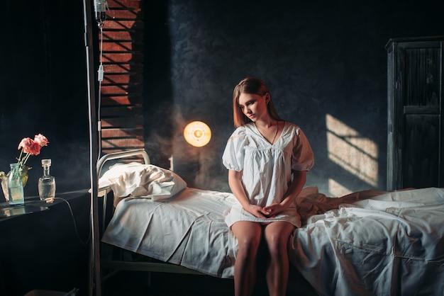 Młoda chora kobieta siedzi na łóżku szpitalnym na kroplówce