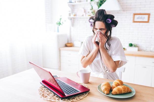 Młoda chora kobieta trzymać tkanki wokół nosa. patrząc na laptopa. chora gospodyni ogląda film. grypa. sam w domu. poranne światło dzienne.