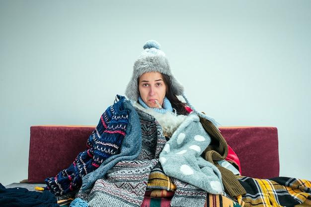 Młoda chora kobieta z kominem siedzi na kanapie w domu lub pracowni przykryta ciepłą dzianiną. choroba, grypa, pojęcie bólu. relaks w domu. koncepcje opieki zdrowotnej.