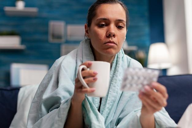Młoda chora kobieta z objawami infekcji w domu