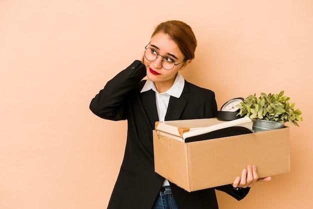 Młoda chuda arabska biznesowa kobieta przenosi pracę na białym tle dotykając tyłu głowy, myśląc i dokonując wyboru.