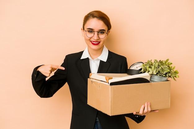 Młoda chuda arabska biznesowa kobieta przenosi pracę na białym tle osoba, wskazując ręką na przestrzeń kopii koszuli, dumna i pewna siebie