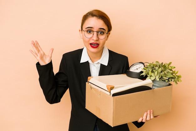 Młoda chuda arabska biznesowa kobieta przenosi pracę na białym tle, otrzymując miłą niespodziankę, podekscytowany i podnoszący ręce.