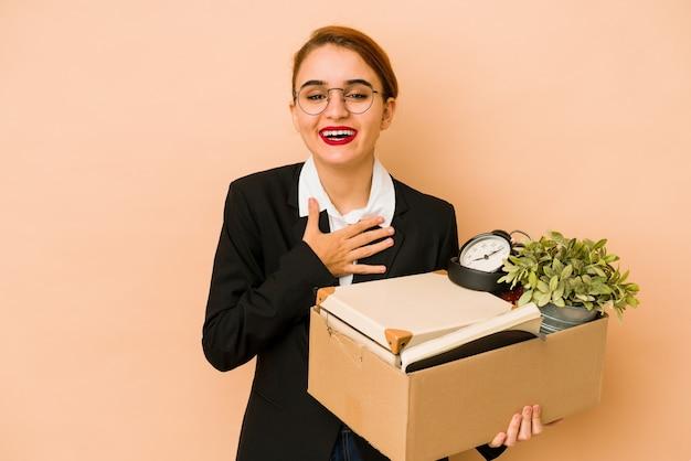 Młoda chuda arabska biznesowa kobieta przenosi pracę na białym tle śmieje się głośno, trzymając rękę na klatce piersiowej.