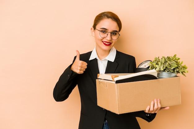 Młoda chuda arabska biznesowa kobieta przenosi pracę na białym tle uśmiechając się i podnosząc kciuk do góry