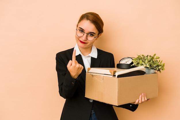 Młoda chuda arabska biznesowa kobieta przenosi pracę na białym tle, wskazując palcem na ciebie, jakby zapraszając, podejdź bliżej.