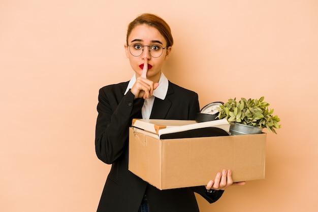 Młoda chuda arabska biznesowa kobieta przenosi pracę na białym tle, zachowując tajemnicę lub prosząc o ciszę.