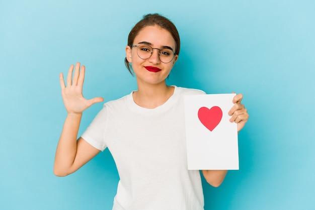 Młoda chuda arabska dziewczyna trzyma kartę walentynki uśmiechnięty wesoły pokazując numer pięć palcami.