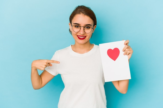 Młoda chuda arabska dziewczyna trzyma kartę walentynkową osobę, wskazując ręką na miejsce na kopię koszuli, dumny i pewny siebie
