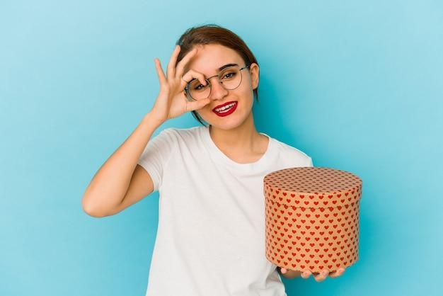 Młoda chuda arabska dziewczyna trzyma pudełko walentynki podekscytowany, utrzymując ok gest na oko.