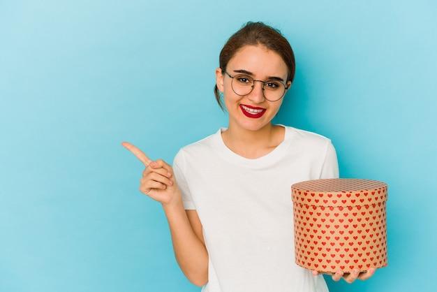 Młoda chuda arabska dziewczyna trzyma pudełko walentynkowe uśmiechając się i wskazując na bok, pokazując coś w pustej przestrzeni.