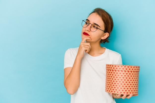 Młoda, chuda arabska dziewczyna trzymająca pudełko walentynkowe, patrząc z ukosa z wątpliwym i sceptycznym wyrazem twarzy.
