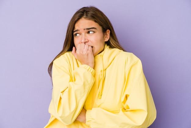 Młoda, chuda dziewczynka kaukaski nastolatek na fioletowym tle gryzie paznokcie, jest nerwowa i bardzo niespokojna.