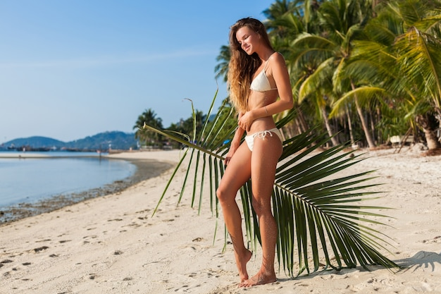 Młoda chuda kobieta w białych strojach kąpielowych bikini trzymając liść palmy, opalając się na tropikalnej plaży.