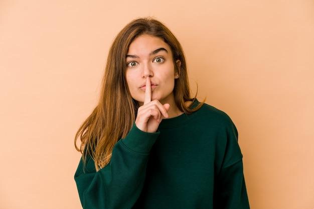 Młoda, chuda nastolatka kaukaska trzymająca w sekrecie lub prosząca o ciszę.