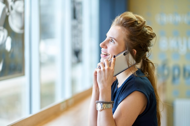 Młoda chuda ruda dziewczyna rozmawia przez telefon i uśmiechając się