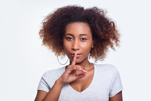 Młoda ciemnoskóra kobieta z kręconymi włosami w jasnej koszulce przyciska palec do ust