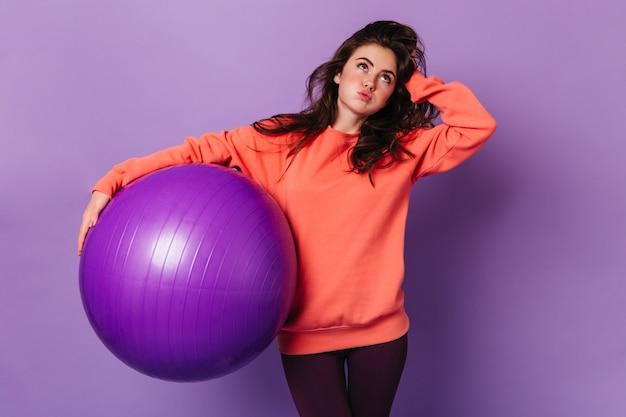 Młoda ciemnowłosa kobieta ciężko wzdycha po treningu z fitballem