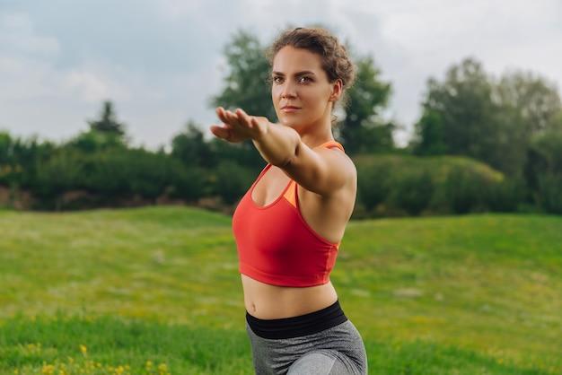 Młoda ciemnowłosa kobieta lubiąca sport czuje się zrelaksowana i rozciąga mięśnie