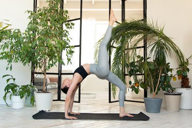Młoda ciemnowłosa kobieta praktykuje jogę rano w swoim domu w pobliżu roślin. kobieta jest zaangażowana w samostanowienie, wykonując ćwiczenia jogi.