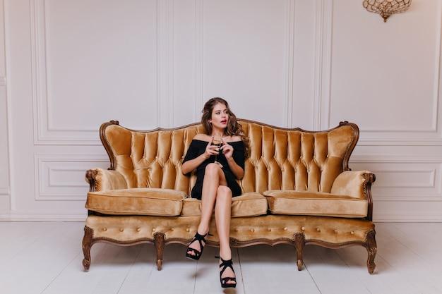 Młoda ciemnowłosa kobieta siedząca na wielkiej złotej sofie otoczona miękkimi poduszkami i spoglądająca w lewo