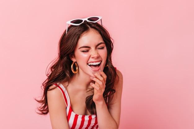 Młoda ciemnowłosa kobieta w świetnym nastroju śmieje się z zamkniętymi oczami na różowej ścianie
