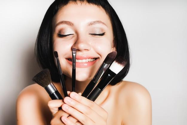 Młoda ciemnowłosa szczęśliwa dziewczyna trzyma pędzle do makijażu, z przyjemnością zamknęła oczy. na białym tle na szarym tle