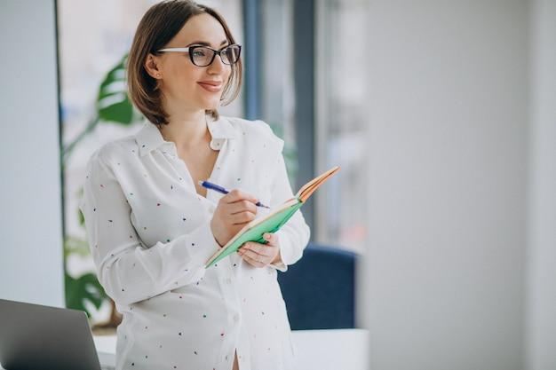 Młoda ciężarna biznesowej kobiety pozycja przy biurem