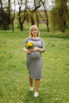 Młoda ciężarna blondynka w szarej sukience, dziewczyna w ciąży na wiosnę na spacer, koncepcja macierzyństwa