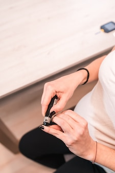 Młoda ciężarna brunetka wykonuje ciążowy autotest cukrzycy w celu kontrolowania poziomu cukru. krwawienie krwi z palca