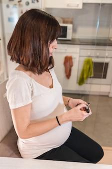 Młoda ciężarna brunetka wykonuje ciążowy autotest cukrzycy w celu kontrolowania poziomu cukru